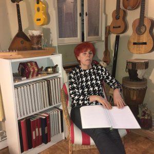 Bild på Sofia som sitter i en fåtölj och läser en punktskriftsbok